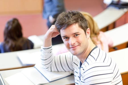 Delighted male student smiling at the camera during an university lesson Stock Photo - 10173883