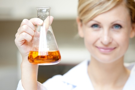 Close-up of a female scientist holding an erlenmeyer and smiling at the camera Stock Photo - 10172118