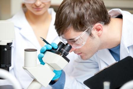 cientificos: Cauc�sica cient�fico masculina con pluma y mirando a trav�s de un microscopio de portapapeles Foto de archivo