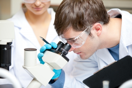 Caucasian male scientist holding pen and clipboard looking through a microscope photo