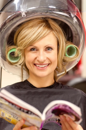 Delighted woman reading a magazine with hair curlers under a hairdryer photo