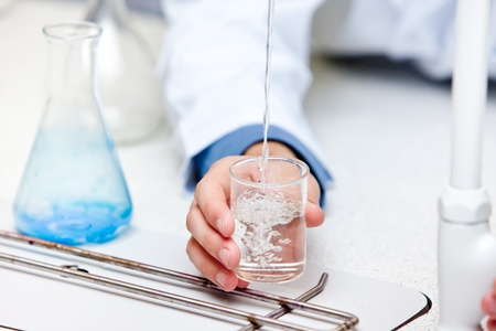 Close-up of a male scientist pouring liquid into a becher Stock Photo - 10163741