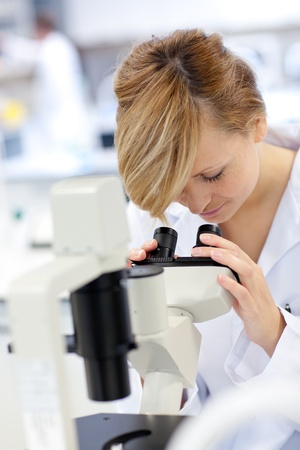 Serious female scientist using a microscope Stock Photo - 10171288