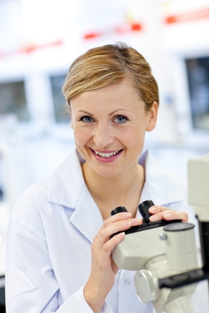 Delighted female scientist using a microscope Stock Photo - 10173115