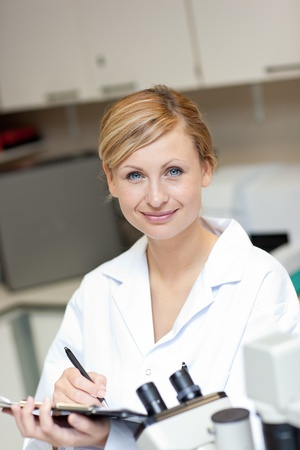Friendly female scientist writing on a clipboard Stock Photo - 10173136