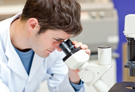 assertive: Assertive male scientist looking through a microscope