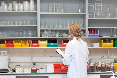 laboratorio clinico: Cient�fica seria escribiendo en su Portapapeles Foto de archivo