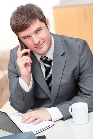 Confident businessman talking on phone and using his laptop in his office photo