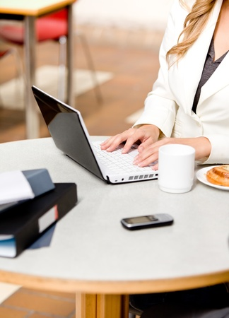 Close-up of a busy businesswoman using her laptop with cellphone, mug and food on the table photo