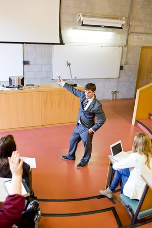 Confident teacher giving a lesson to university students photo