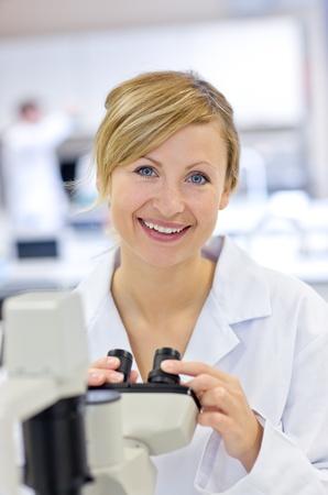 Joyful female scientist using a microscope Stock Photo - 10171456