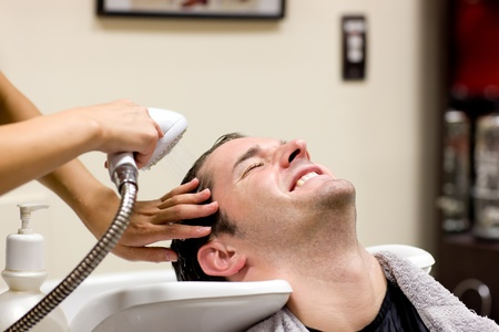 Handsome man having his hair washed Stock Photo - 10171291