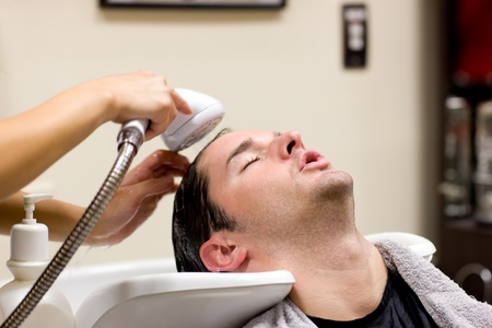 Young caucasian man having his hair washed photo