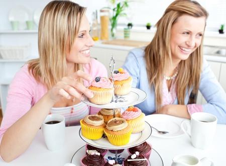 Women having fun eating cupcakes in the kitchen photo