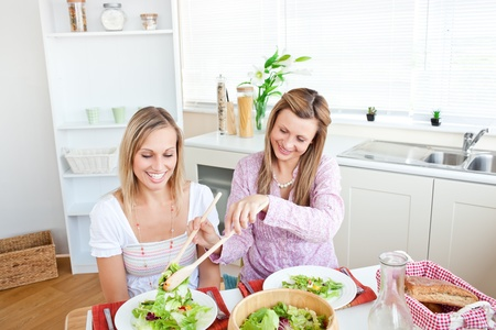 frienship: Adorable woman serving salad to her friend sitting at a table during lunchtime