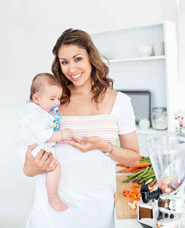 Portrait of a radiant mother holding her baby after preparing the lunch Stock Photo - 10163681