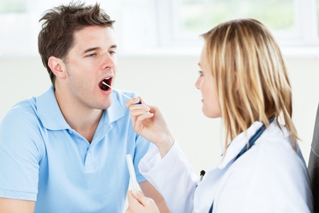 saliva: Caucasian female doctor taking a saliva sample of a male patient using cotton-bud