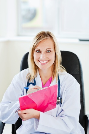 Portrait of a beautiful doctor writing down notes using a clipboard Stock Photo - 10163030