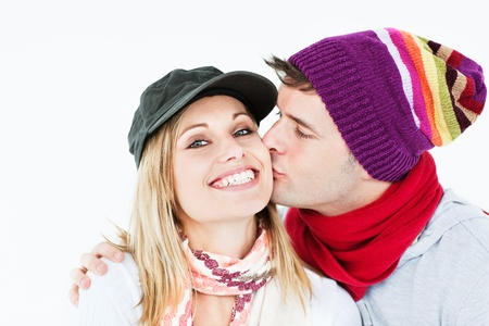 Beautiful woman receiving a kiss from her boyfriend wearing both cap and hat photo