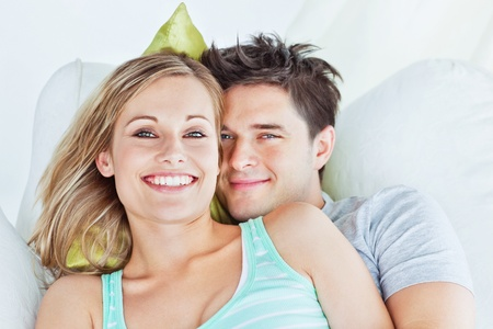 lying on couch: Portrait of an attractive couple hugging and relaxing on the sofa