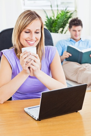 Happy woman with a cup of coffee using laptop with her boyfriend reading on the sofa photo