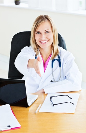 Joyful female doctor ready to shake hands with a patient Stock Photo - 10163385