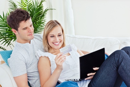 Happy couple with credit card and laptop resting on the sofa during the day photo