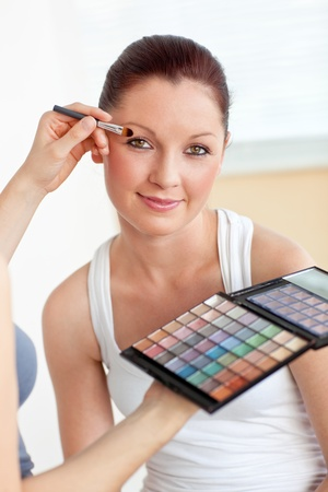 Make-up artist putting some eye-shadow on a beautiful woman photo