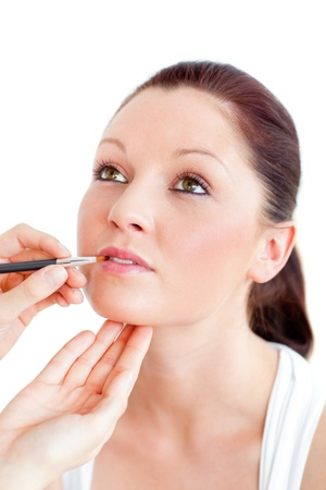 Concentrated woman being make-up by a professional artist photo