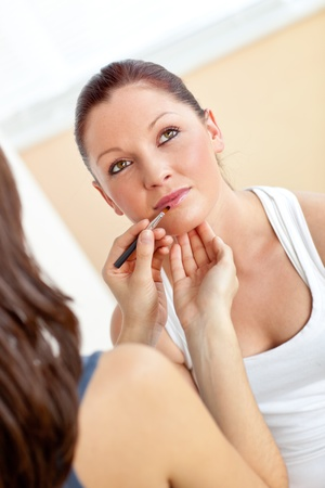 Young woman making-up her friend using lipstick and eye shadow  photo