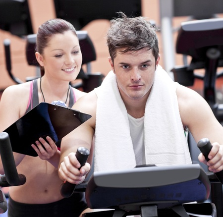 Smart female coach taking notes while her pupil is pedaling on a bicycle photo