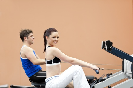 rower: Positive woman with her boyfriend using a rower in a sport centre