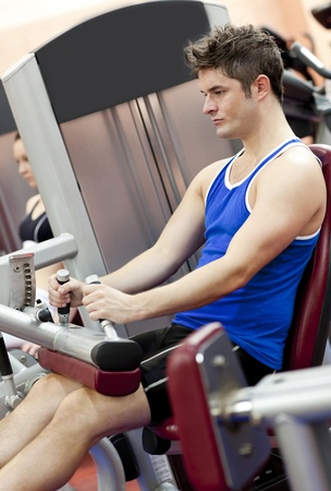 muskeltraining: Serious athletischer Mann mit einer Beinpresse im Kraftraum eines Sportzentrums Lizenzfreie Bilder