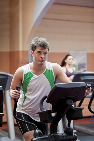 Handsome man doing exercises using cross trainer in a fitness centre photo