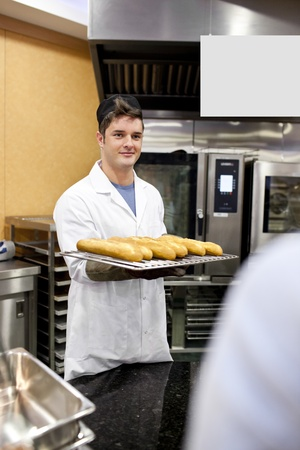 Young baker holding baguettes and breads standing in the kitchen of a cafeteria photo