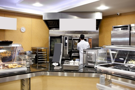 View of a kitchen with baker preparing breads and baguettes in a cafeteria photo