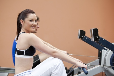 Happy woman with her boyfriend using a rower in a fitness centre photo