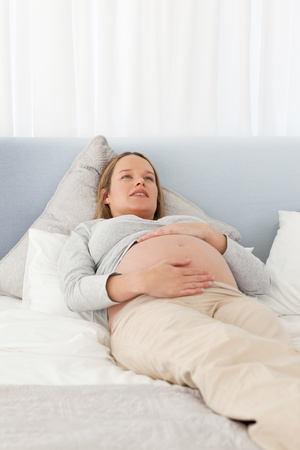 Pretty pregnant woman resting on a bed Stock Photo - 10169828