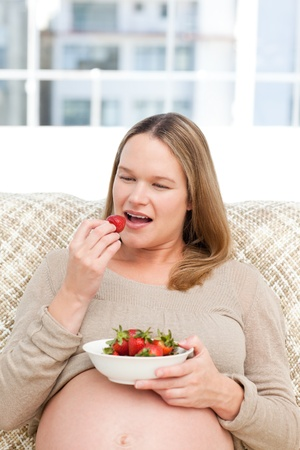 Hungry pregnant woman eating strawberries sitting in the living-room photo