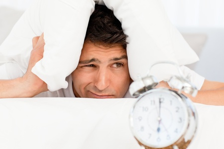 exasperated: Handsome man putting his head under the pillow Stock Photo