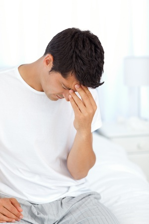 exhausting: Attractive man having a headache and touching his forehead  Stock Photo
