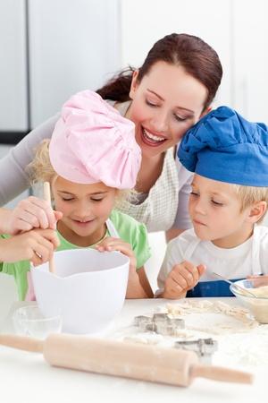 ni�os cocinando: Madre con sus hijos para hornear juntos en la cocina Foto de archivo