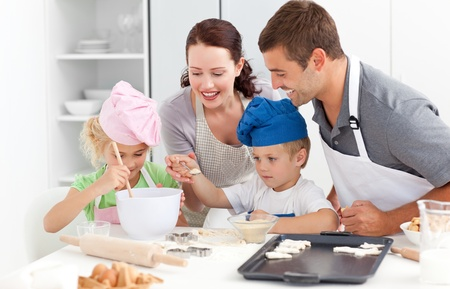 Happy family cooking a cream together in the kitchen  photo
