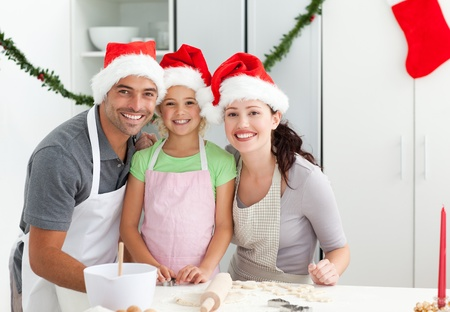 holiday cooking: Portrait of a man with wife and daughter cooking Christmas biscuits