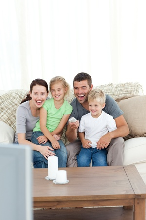 woman couch: Happy family laughing while watching television sitting on the sofa