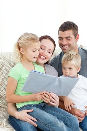 Adorable familia leyendo un libro juntos en la sala de estar
