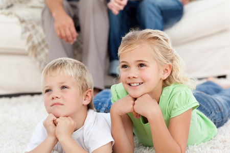 Brother and sister watching television on the floor with their parents  photo