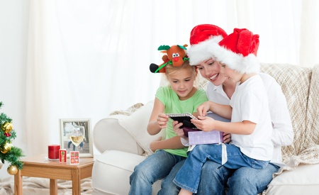 Mother and children looking at a calendar sitting on the sofa Stock Photo - 10172504