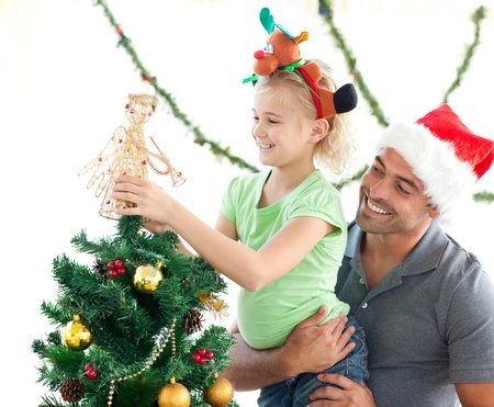 Cute little girl decorating the christmas tree with her father photo