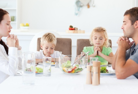 Portrait of a family praying together during the lunch photo